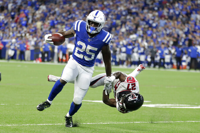 Indianapolis Colts running back Marlon Mack (25) runs past Atlanta Falcons strong safety Damontae Kazee (27) for a touchdown during the second half of an NFL football game, Sunday, Sept. 22, 2019, in Indianapolis. (AP Photo/Michael Conroy)
