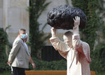 A visitor to the National Museum walks past a new statue of the late pope, St. John Paul II, throwing a stone at a