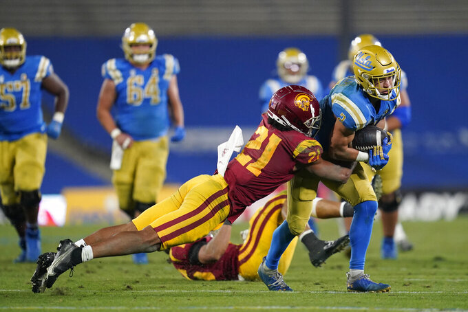 Southern California safety Isaiah Pola-Mao (21) tackles UCLA wide receiver Kyle Philips (2) during the fourth quarter of an NCAA college football game Saturday, Dec 12, 2020, in Pasadena, Calif. (AP Photo/Ashley Landis)
