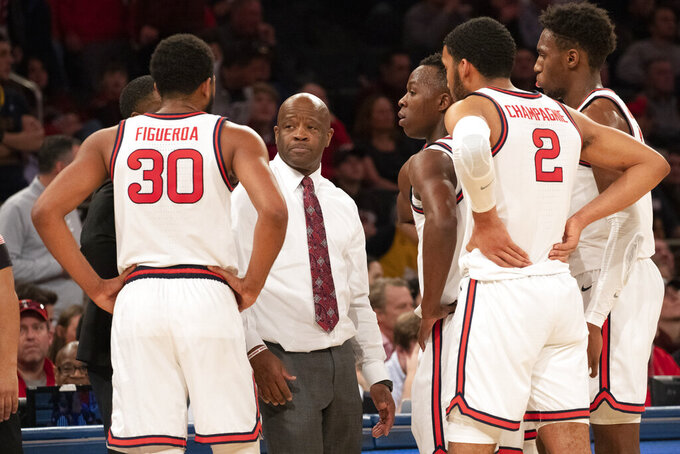 St. John's head coach Mike Anderson speaks with players LJ Figueroa (30) and Julian Champagne (2) during a timeout in the second half of an NCAA college basketball game against West Virginia, Saturday, Dec. 7, 2019 in New York. St. John's won 70-68. (AP Photo/Mark Lennihan)