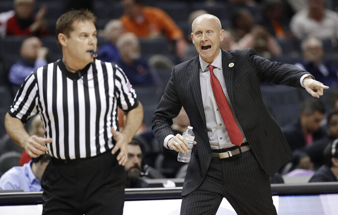 Louisville head coach Chris Mack, right, shouts at an official during the first half of an NCAA college basketball game against Notre Dame in the Atlantic Coast Conference tournament in Charlotte, N.C., Wednesday, March 13, 2019. (AP Photo/Chuck Burton)