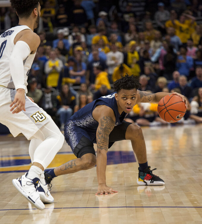 Georgetown guard James Akinjo, right, is guarded by Marquette guard Markus Howard, left, during the second half of an NCAA college basketball game Saturday, March 9, 2019, in Milwaukee. Georgetown beat Marquette 86-84. (AP Photo/Darren Hauck)