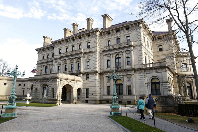 FILE - In this Dec. 1, 2014, file photo, visitors walk toward an entrance to The Breakers mansion in Newport, R.I.  The Preservation Society of Newport County says it's closing the famed Gilded Age mansion for three months starting Monday, March 1, 2021 But there's good news for mansion aficionados Marble House, a popular Newport destination and National Historic Landmark that's been closed since last March because of the coronavirus pandemic, is reopening to visitors. (AP Photo/Steven Senne, File)