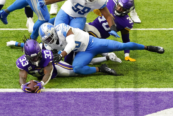 Minnesota Vikings running back Dalvin Cook (33) scores on a 5-yard touchdown run in front of Detroit Lions safety Duron Harmon (26) during the first half of an NFL football game, Sunday, Nov. 8, 2020, in Minneapolis. (AP Photo/Jim Mone)