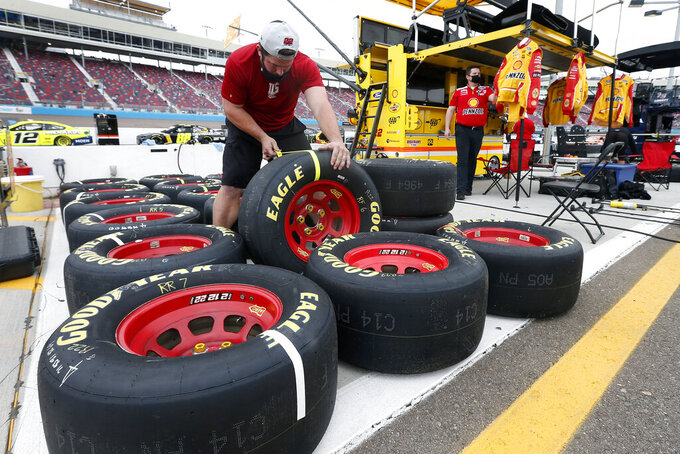 A pit crew member for driver Joey Logano prepares race tires prior to a NASCAR Cup Series auto race at Phoenix Raceway, Sunday, Nov. 8, 2020, in Avondale, Ariz. (AP Photo/Ralph Freso)