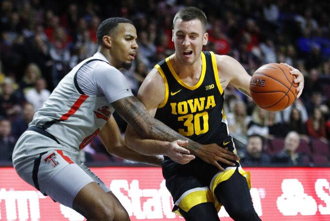 Iowa's Connor McCaffery (30) drives around Texas Tech's Kyler Edwards (0) during the second half of an NCAA college basketball game Thursday, Nov. 28, 2019, in Las Vegas. (AP Photo/John Locher)