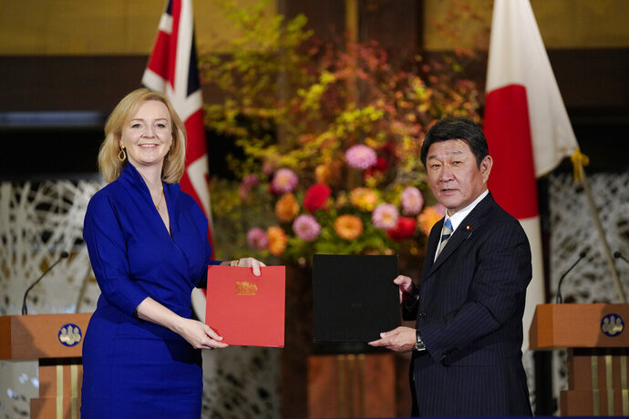 British International Trade Secretary Liz Truss, left, and Japanese Foreign Minister Toshimitsu Motegi exchange agreement documents for economic partnership between Japan and Britain at Iikura Annex of the Foreign Ministry in Tokyo, Friday, Oct. 23, 2020. Japan and Britain signed a bilateral free trade deal Friday in the the first such major post-Brexit deal, reducing tariffs on Yorkshire lamb sold in Japan, as well as auto parts for Japan's Nissan plant. (Kimimasa Mayama/Pool Photo via AP)