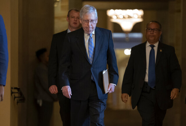 Senate Majority Leader Mitch McConnell, R-Ky., walks to the chamber as lawmakers negotiate on the emergency coronavirus response legislation, at the Capitol in Washington, Wednesday, March 18, 2020. (AP Photo/J. Scott Applewhite)