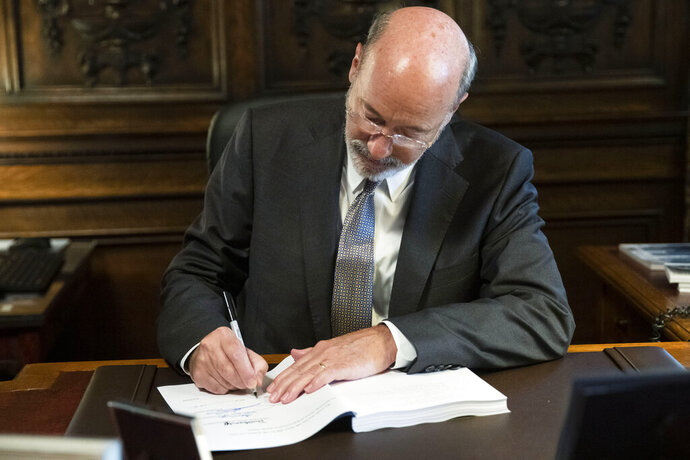Pennsylvania Gov. Tom Wolf signs the main appropriations bill in a $34 billion budget package that passed the Legislature this week at the state Capitol in Harrisburg, Pa., Friday, June 28, 2019. (AP Photo/Matt Rourke)
