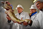 Britain's Prime Minister and Conservative Party leader Boris Johnson, center, visits Grimsby fish market in Grimsby, northeast England, Monday Dec. 9, 2019, ahead of the general election on Dec. 12. All 650 seats in the House of Commons are up for grabs Thursday when voters will pass judgement on a divisive election that will determine Britain's future with European Union. (Ben Stansall/Pool via AP)