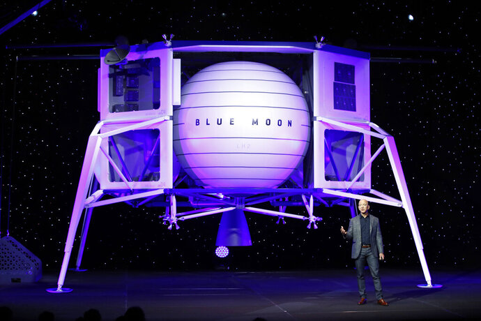 FILE - In this, May 9, 2019, file photo, Jeff Bezos speaks in front of a model of Blue Origin's Blue Moon lunar lander in Washington. Bezos and Virgin Galactic's Richard Branson favor going back to the moon before Mars. SpaceX's Elon Musk also is rooting for the moon, although his heart's on Mars. (AP Photo/Patrick Semansky, File)