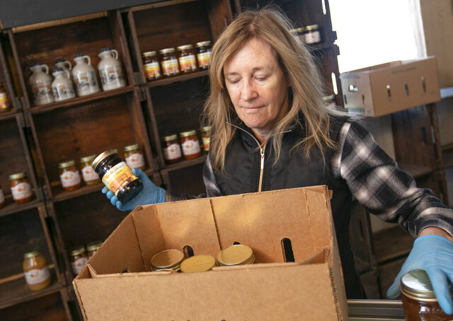 Linda DeFrancesco stocks shelves with her farm's own salsa, spreads, veggies and salsa at DeFrancesco Farm Stand in Northford, Conn., Thursday, March 26, 2020. Businesses across the state are worried about the impact of the coronavirus, even the ones considered
