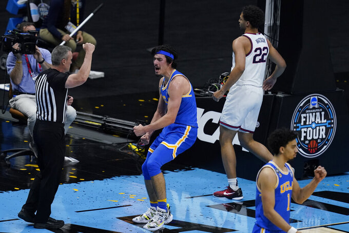 UCLA guard Jaime Jaquez Jr., center, celebrates in front of Gonzaga forward Anton Watson (22) after making a basket during the first half of a men's Final Four NCAA college basketball tournament semifinal game, Saturday, April 3, 2021, at Lucas Oil Stadium in Indianapolis. (AP Photo/Darron Cummings)