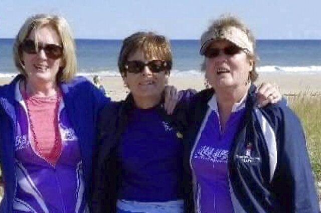 In this Sept. 2018 photo, Joanne Mellady, right, poses with her sisters Jean Sinofsky, left, and Joyce Smith, center, at a Massachusetts beach on Cape Cod during a bike trek fundraiser for Alpha 1.org. Mellady, who received a double lung transplant in 2007, died of the coronavirus in March 2020. (Ed Sinofsky via AP)