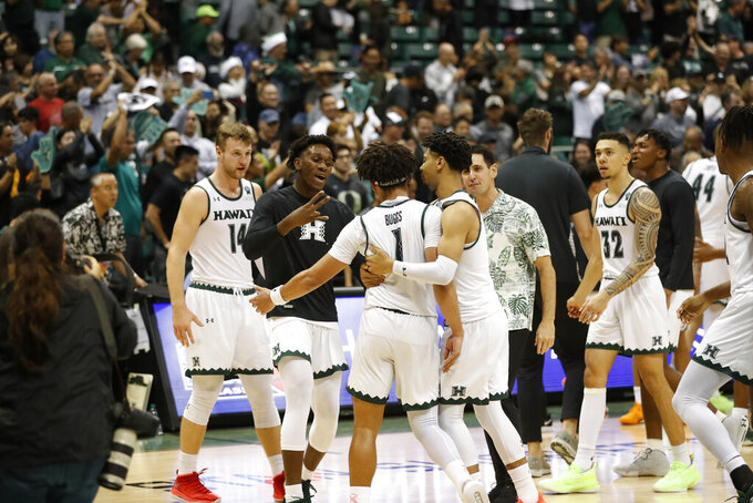 Hawaii players celebrate after defeating UTEP in an NCAA college basketball game Sunday, Dec. 22, 2019, in Honolulu. Hawaii defeated UTEP 67-63 advancing to the semifinals of the tournament. (AP Photo/Marco Garcia)