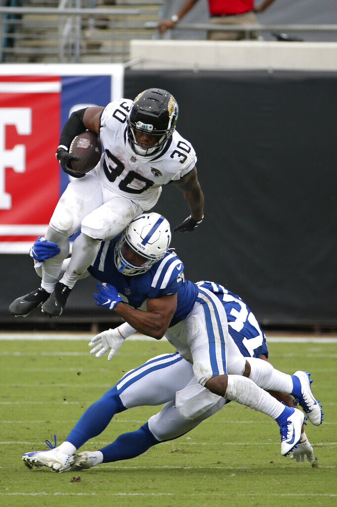Jacksonville Jaguars running back James Robinson (30) leaps for yardage over Indianapolis Colts cornerback Isaiah Rodgers, center, and safety Khari Willis, back right, during the second half of an NFL football game, Sunday, Sept. 13, 2020, in Jacksonville, Fla. (AP Photo/Stephen B. Morton)