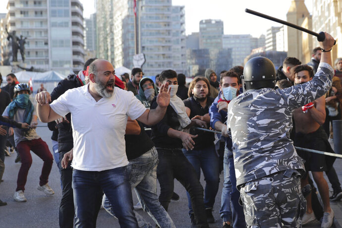 Riot police swing batons at anti-government protesters during clashes during a protest in downtown Beirut, Lebanon, Tuesday, Nov. 19, 2019. Scuffles have broken out in central Beirut as hundreds of anti-government protesters tried to prevent lawmakers from reaching Parliament. (AP Photo/Hassan Ammar)
