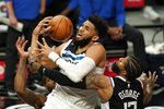 Minnesota Timberwolves center Karl-Anthony Towns, center, has the ball knocked from his hands by Los Angeles Clippers guard Paul George, right, as forward Kawhi Leonard defends during the second half of an NBA basketball game Sunday, April 18, 2021, in Los Angeles. (AP Photo/Mark J. Terrill)