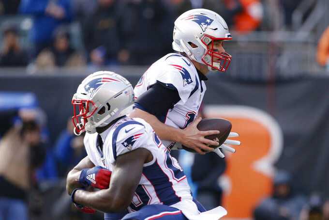 New England Patriots quarterback Tom Brady, right, fakes a handoff to running back James White, left, in the first half of an NFL football game against the Cincinnati Bengals, Sunday, Dec. 15, 2019, in Cincinnati. (AP Photo/Gary Landers)