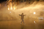An anti-government protester is sprayed by a water canon during ongoing protests against the political elites who have ruled the country since decades, in Beirut, Lebanon, Sunday, Jan. 19, 2020. Lebanese security forces used tear gas, water cannons and rubber bullets in clashes with hundreds of anti-government protesters outside the country's Parliament on Sunday, as violence continued to escalate in a week of rioting in the capital. (AP Photo/Hassan Ammar)