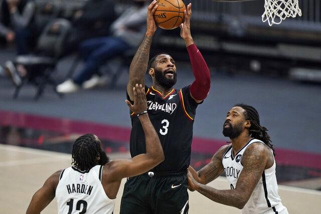 Cleveland Cavaliers' Andre Drummond (3) drives to the basket against Brooklyn Nets' James Harden (13) and DeAndre Jordan (6) during the first half of an NBA basketball game Friday, Jan. 22, 2021, in Cleveland. (AP Photo/Tony Dejak)