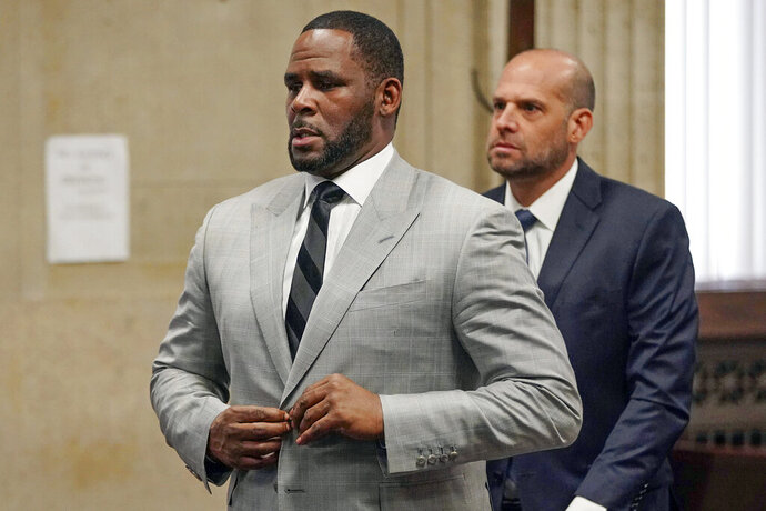 FILE - In this June 6, 2019, file photo, singer R. Kelly pleaded not guilty to 11 additional sex-related felonies during a court hearing before Judge Lawrence Flood at Leighton Criminal Court Building in Chicago. An updated federal indictment filed on Friday, Feb. 14, 2020, in Chicago, refers to yet another minor accusing R. Kelly of sexual misconduct, adding to the jailed singer's mounting legal challenges across three states. (E. Jason Wambsgans/Chicago Tribune via AP, Pool, File)