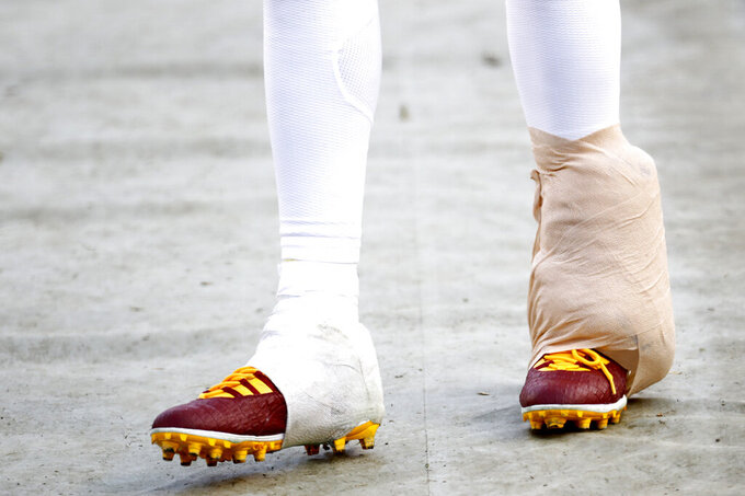 The leg of Washington Redskins quarterback Dwayne Haskins is seen taped up as he walks on the sideline during the second half of an NFL football game against the New York Giants, Sunday, Dec. 22, 2019, in Landover, Md. (AP Photo/Patrick Semansky)