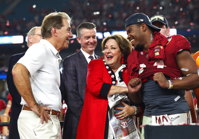 Alabama running back Damien Harris (34) and Terry Saban, laugh with Alabama head coach Nick Saban, during the Orange Bowl NCAA college football game trophy presentation, Sunday, Dec. 30, 2018, in Miami Gardens, Fla. Alabama defeated Oklahoma 45-34. (AP Photo/Wilfredo Lee)