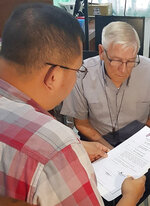In this Dec. 5, 2018, photo released by the Bureau of Immigration Public Information Office, American Roman Catholic priest Rev. Kenneth Bernard Hendricks, right, looks at documents after being arrested in a church in Naval town in the island province of Biliran, central Philippines. Philippine immigration authorities say they have arrested Hendricks accused of sexually assaulting altar boys in a remote central town in a case one official described as