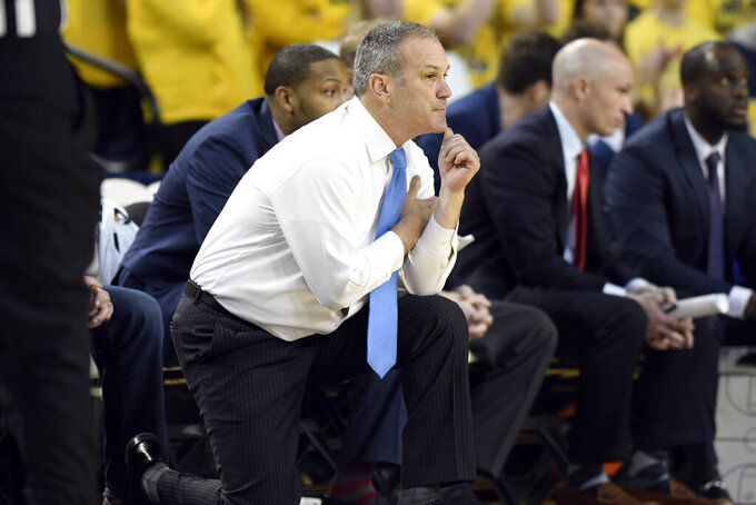 UMass-Lowell head coach Pat Duquette, front, watches his team play against Michigan during the first half of an NCAA college basketball game, Sunday, Dec. 29, 2019, in Ann Arbor, Mich. (AP Photo/Jose Juarez)