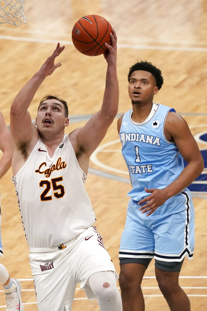 Loyola of Chicago's Cameron Krutwig (25) heads to the basket as Indiana State's Tre Williams (1) watches during the second half of an NCAA college basketball game in the semifinal round of the Missouri Valley Conference men's tournament Saturday, March 6, 2021, in St. Louis. (AP Photo/Jeff Roberson)