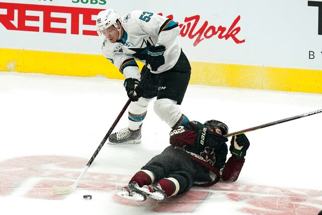 San Jose Sharks defenseman Nicolas Meloche (53) gets the puck after sending Arizona Coyotes right wing Clayton Keller, right, to the ice during the first period of an NHL hockey game Thursday, Jan. 14, 2021, in Glendale, Ariz. (AP Photo/Ross D. Franklin)
