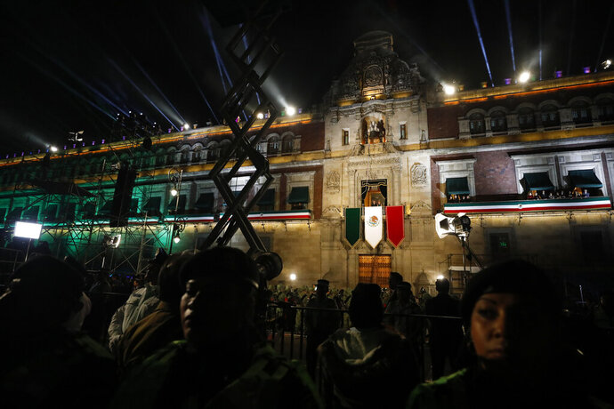 Police provide a security cordon as President Andres Manuel Lopez Obrador and first lady Beatriz Gutierrez Muller look out toward the crowd from the balcony of the National Palace, after Lopez Obrador gave the annual independence shout to kick of Independence Day celebrations at the Zocalo in Mexico City, Sunday, Sept. 15, 2019. Every year the Mexican president marks the
