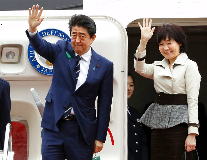 Japanese Prime Minister Shinzo Abe waves with his wife Akie Abe while boarding his plane before departure for the U.S. at Haneda international airport in Tokyo Tuesday, April 17, 2018. Abe is heading to U.S. President Donald Trump's Mar-a-Lago resort for two days of talks, hoping to keep Japan's interests on the table in a possible U.S.-North Korea summit as well as stem a slide in his voter support ratings. (Kenzaburo Fukuhara/Kyodo News via AP)