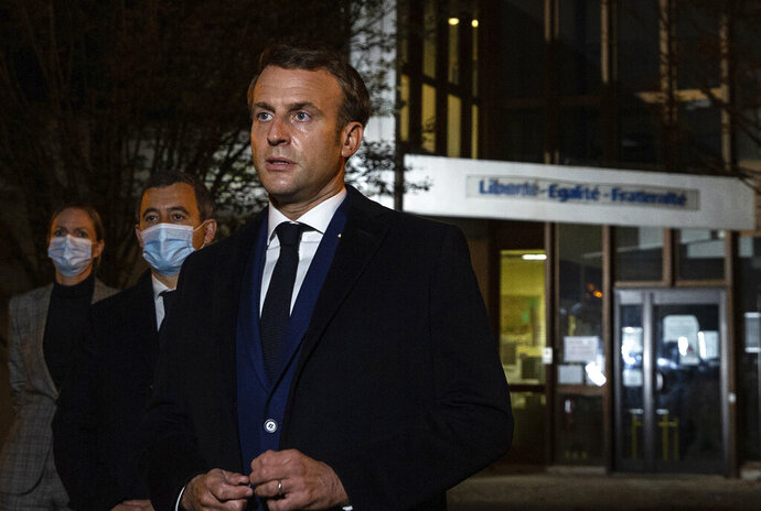 French President Emmanuel Macron, flanked by French Interior Minister Gerald Darmanin, second left, speaks in front of a high school Friday Oct.16, 2020 in Conflans Sainte-Honorine, northwest of Paris, after a history teacher who opened a discussion with high school students on caricatures of Islam's Prophet Muhammad was beheaded. French President Emmanuel Macron denounced what he called an