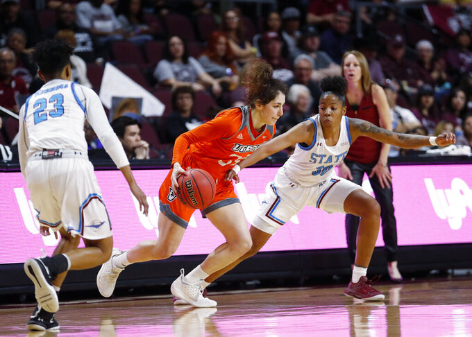 Texas-Rio Grande Valley forward Megan Johnson (34) moves the ball between New Mexico State guard Aaliyah Prince (23) and Gia Pack (30) during a NCAA college basketball Western Athletic Conference Women's Tournament championship game Saturday, March 16, 2019, in Las Vegas. (AP Photo/Steve Marcus)