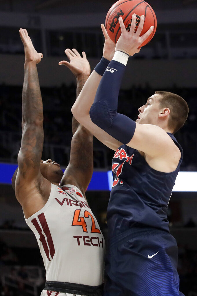 Liberty forward Scottie James, right, shoots over Virginia Tech guard Ty Outlaw during the first half of a second-round game in the NCAA men's college basketball tournament Sunday, March 24, 2019, in San Jose, Calif. (AP Photo/Jeff Chiu)