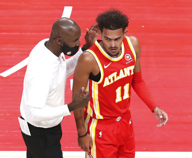 Atlanta Hawks coach Lloyd Pierce confers with Trae Young during the first half of the team's NBA basketball game against the Detroit Pistons on Monday, Dec. 28, 2020, in Atlanta. (Curtis Compton/Atlanta Journal-Constitution via AP)