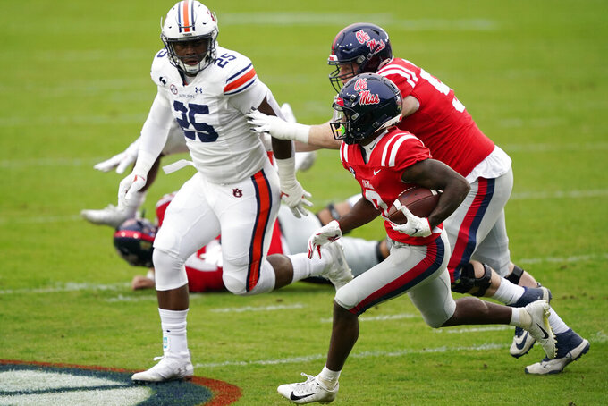 Mississippi wide receiver Elijah Moore (8) runs past Auburn linebacker Colby Wooden (25) for a first down during the first half of an NCAA college football game in Oxford, Miss., Saturday Oct. 24, 2020. Auburn won 35-28. (AP Photo/Rogelio V. Solis)