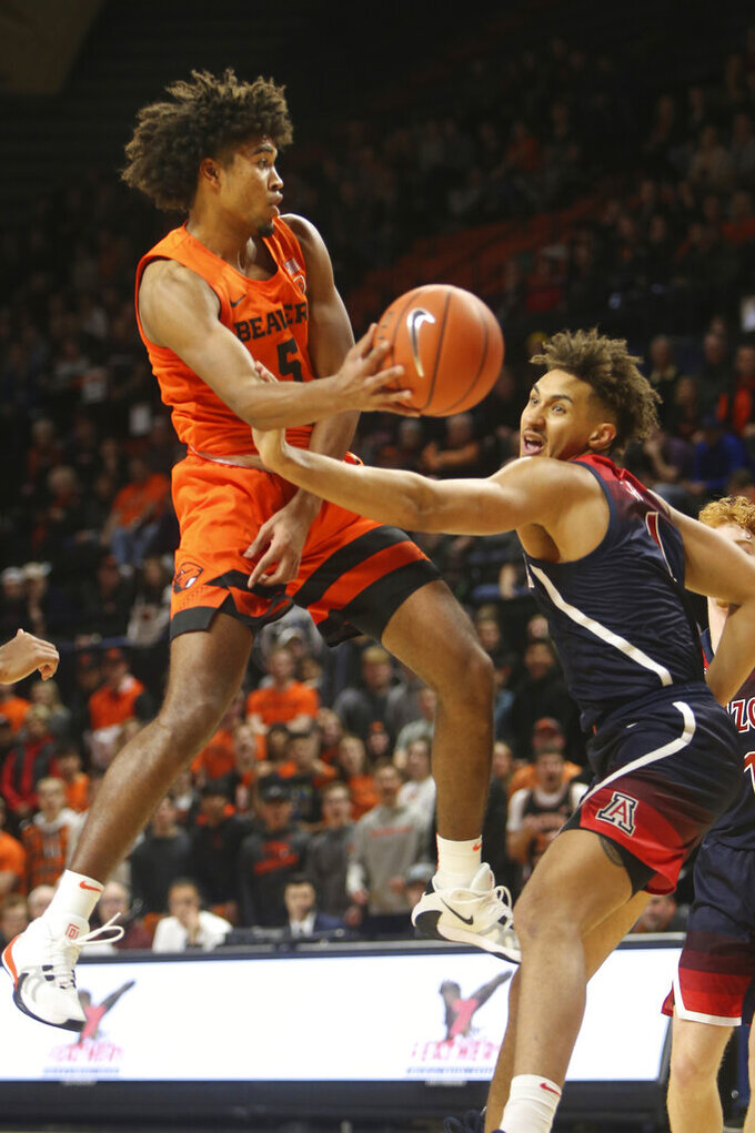 Oregon State's Ethan Thompson, left, passes the ball under pressure from Arizona's Chase Jeter, right, during the second half of an NCAA college basketball game in Corvallis, Ore., Sunday, Jan. 12, 2020. (AP Photo/Chris Pietsch)