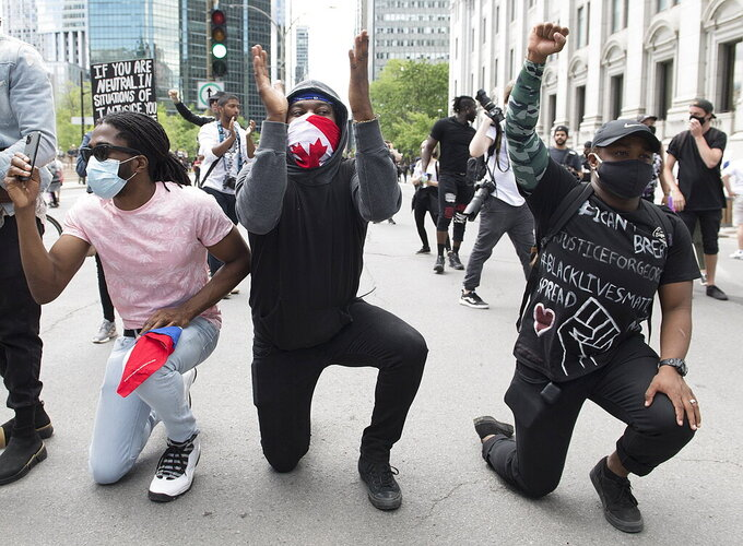 Protesters take a knee during a demonstration calling for justice for the death of George Floyd and all victims of police brutality, in Montreal, Sunday, June 7, 2020. Floyd died after being restrained by Minneapolis police officers on May 25. (Graham Hughes/The Canadian Press via AP)