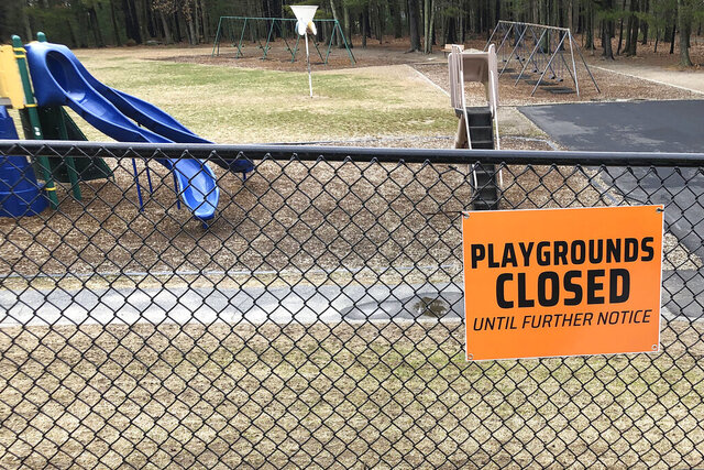 FILE - This Friday, March 20, 2020 file photo shows a closed sign near an entrance to a playground at an elementary school in Walpole, Mass., amid the COVID-19 coronavirus outbreak. Child welfare agencies in the U.S. have a difficult mission in the best of times, and now they're scrambling to confront new challenges during the coronavirus outbreak. (AP Photo/Steven Senne)