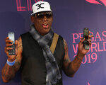 FILE - In this Jan. 26, 2019, file photo, Dennis Rodman poses with two flip phones on the blue carpet at the Pegasus World Cup Invitational Horse Race at Gulfstream Park in Hallandale Beach, Fla. The owner of a Southern California yoga studio is accusing Dennis Rodman of helping three people steal more than $3,500 in merchandise from his business. Ali Shah says security cameras captured the former NBA star walking into Vibes Hot Yoga in Newport Beach on Tuesday, May 7, 2019, with his alleged accomplices. (AP Photo/Lynne Sladky, File)