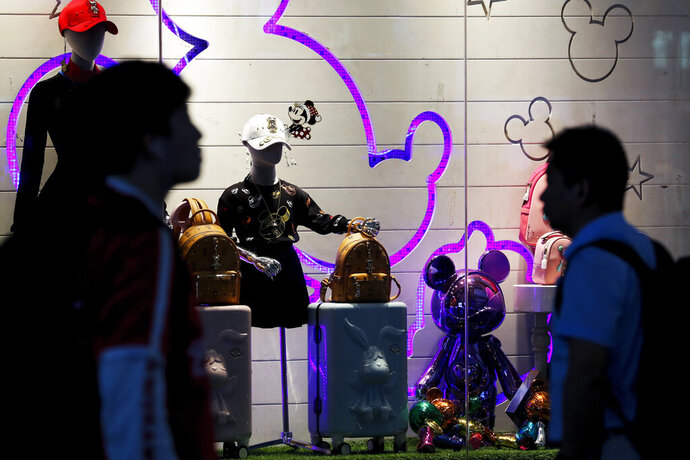 Passengers walk by merchandise on display at the Shanghai Disney flagship store at Hongqiao Railway Station in Shanghai, China, Monday, Oct. 14, 2019. China's trade with the United States fell by double digits again in September amid a tariff war that threatens to tip the global economy into recession. (AP Photo/Andy Wong)