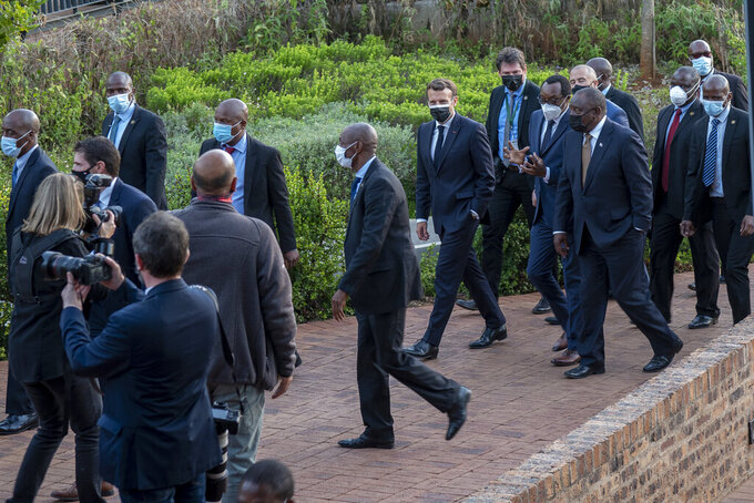 French President Emmanuel Macron, center, and South African President Cyril Ramaphosa arrive at the University of Pretoria Future Africa in Pretoria, South Africa, Friday May 28, 2021. Macron and Ramaphosa are launching a program to support African vaccine production, a project backed by the European Union, the United States and the World Bank. (AP Photo/Jerome Delay)