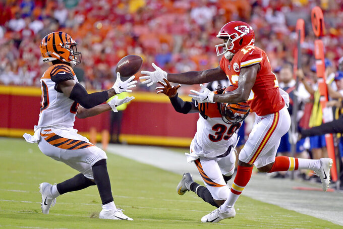 Cincinnati Bengals safety Brandon Wilson, left, catches a pass intended for Kansas City Chiefs wide receiver Byron Pringle (13) but the interception was called back due to pass interference by Tony Lippett (39) during the first half of an NFL preseason football game in Kansas City, Mo., Saturday, Aug. 10, 2019. (AP Photo/Ed Zurga)