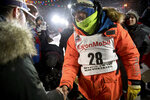 FILE - In this March 13, 2019, file photo, Joar Leifseth Ulsom, right, wearing a bib with ExxonMobil lettering on it, congratulates Peter Kaiser on his win in the Iditarod Trail Sled Dog Race in Nome, Alaska. The world's most famous sled dog race has lost another major sponsor as the Iditarod prepares for a scaled-back version of this year's race because of the pandemic, officials said Thursday, Jan. 21, 2021. ExxonMobil confirmed to The Associated Press that the oil giant will drop its sponsorship of the race. (Marc Lester/Anchorage Daily News via AP, File)