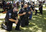 Fairfield police officers kneel during