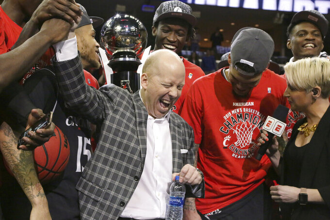FILE - In this March 17, 2019, file photo, Cincinnati coach Mick Cronin high-fives one of his players at the trophy ceremony after Cincinnati beat Houston in the championship game of the American Athletic Conference men's tournament, in Memphis, Tenn. Cronin has been hired as UCLA's basketball coach, ending a months-long search to find a replacement for the fired Steve Alford. The university says Cronin agreed to a $24 million, six-year deal on Tuesday, April 9, 2019. (AP Photo/Troy Glasgow, File)