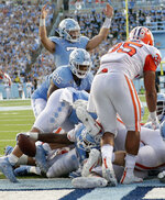 North Carolina Tar Heels's Sam Howell (7) signals for a touchdown as J.C. Chalk (25) crosses the line to score late in the fourth quarter of an NCAA college football game against Clemson in Chapel Hill, N.C., Saturday, Sept. 28, 2019. North Carolina's Carl Tucker (86) and Clemson Justin Foster (35) are also in on the play. (AP Photo/Chris Seward)